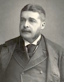 Head and shoulders of Sullivan, dressed in a dark suit, facing slightly left of center, with moustache and long sideburns. Black and white.