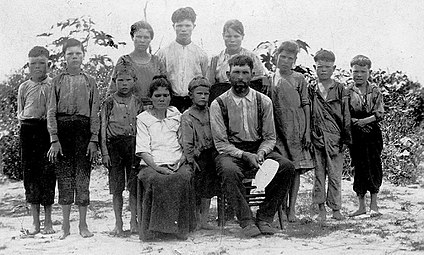 Outdoor scene of a man and woman seated on chairs in front of a group of ten children of varying ages, barefoot and wearing simple clothing