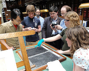 Photograph of students gathered around a museum keeper, who is showing them a Dürer print block made of pear wood