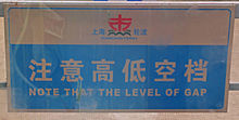 "A light-colored sign with Chinese characters and ""Note that the level of gap"" written on it in blue"