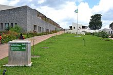 Photograph depicting a hospital building, with Rwandan flag, viewed from the entrance pathway