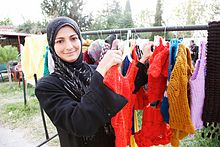 A Syrian refugee stands next to the clothes she has knitted for sale.