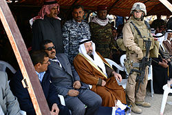 A Marine officer standing with a group of Iraqis, some in suits, some in traditional garb, and some in military uniforms.