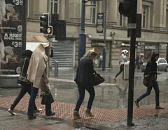 Women rushing to get out of the rain.