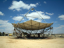 A horizontal parabolic dish, with a triangular structure on its top.
