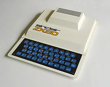 "View of the ZX80, a white rectangular computer with a black keyboard with blue keys and the words ""SINCLAIR ZX80"" on the centre left of the case, in front of a large bulge at the rear of the machine."