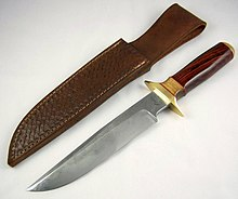 Large knife with polished wooden handle, lying next to a leather sheath
