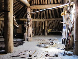Earth lodge interior showing the central wooden pillars, wooden walls, a packed clay floor, a fire pit, back rests, a table with food, a fur rug, cattail mats, various other furnishings, and a canopy bed