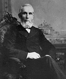Monochrome photograph of Alexander Mackenzie sitting in a chair