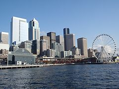 Vew of the downtown Seattle skyline, on the waterfront, with the Seattle Aquarium on the left and Seattle Great Wheel on the right.
