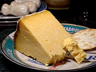 A wedge of yellow-white cheese, with a large crumbly piece broken off, served with a cracker