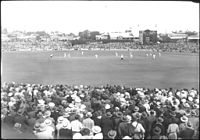 Full crowd in attendance at the first Test, Brisbane Cricket Ground, Bradman and Fingleton batting, 1936-37 Marylebone Cricket Club (MCC) tour of Australia (16592562176).jpg