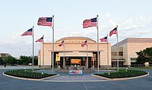 "Above the doorway of a large, relatively plain rectangular structure with a short dome are the words ""George Bush Library."" In front of the building is a circular courtyard with a water fountain; eight American flags are positioned evenly around the circle."