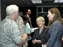 Two adult women talk with an older white-haired man in camouflage inside a dark room.