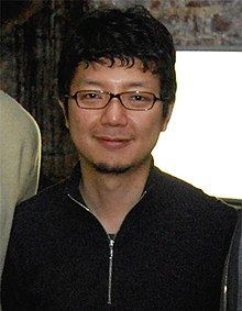 A portrait shot of a middle-aged Asian man with short, messy black hair, glasses and a zip-up sweatshirt