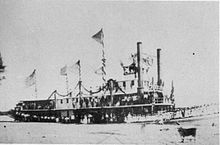 Black and white photograph of a docked sternwheeler with two funnels
