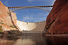 The Glen Canyon Dam and bridge, seen from the calm surface of the river at its base.