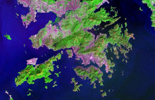 Topographical satellite image with enhanced colours showing areas of vegetation and conurbation. Purple areas around the coasts indicate the areas of urban development