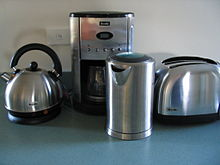 two electric kettles, a drip coffee maker, and a toaster on a table top
