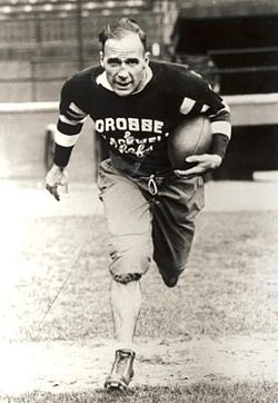 "A football player in his mid thirties is seen running toward the camera with a ball tucked under his left arm. He balding, and wearing a dark coloured uniform with the words ""Crosse and Blackwell Chefs"" on his chest."