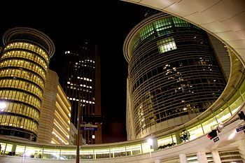 Night image of several tall skyscrapers taken from a street view, looking up. Several lights and traffic lights can be seen on the street, along with a round walkway above the street.