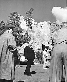 Image of Hitchcock pictured under Mount Rushmore during the filming of North by Northwest