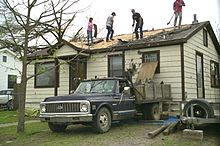 People working to clear debris off of a damaged home