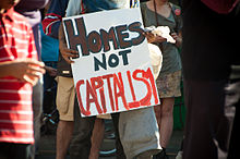 "Photograph of a protestor holding a sign saying, ""HOMES NOT CAPITALISM"""