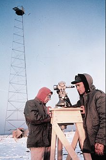 Picture of a man taking measurements with a theodolite in a frozen environment.