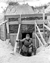 Mussolini climbing steps out of a bunker