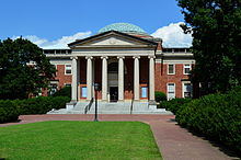 A brick building with a rusted dome and ionic columns.