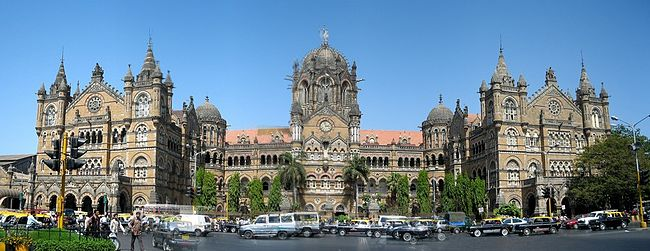 A brown building with clock towers, domes and pyramidal tops. Also a busiest railway station in India.[299] A wide street in front of it