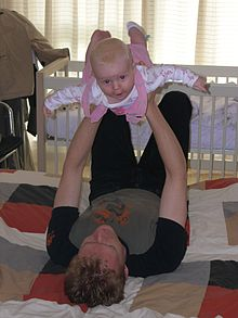 A young father lies on his back on a quilt on the floor. He holds his baby daughter up above him with his arms straight and his hands round her ribcage. The baby has her arms and legs stretched out and arches her back smiling directly at the camera.