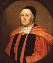 An elderly man with some strands of white hair visible from beneath a close-fitting black cap; he is wearing red and black robes with a red academical hood and broad white bands at his collar