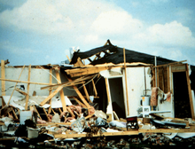 Significant tornado damage inflicted upon a home, with its exterior walls missing and some of its interior walls and roof destroyed