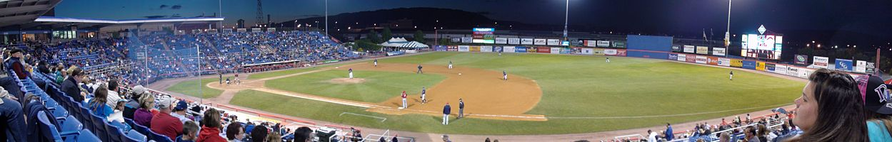 A night baseball game in progress in a small outdoor baseball stadium.