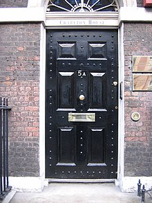 A black front door located on an old red brick building. There is a letter slot built into the door approximately 3 feet or 90 centimetres from the bottom.