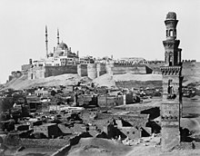 A multi-domed mosque dominates the walled Citadel, with ruined tombs and a lone minaret in front.