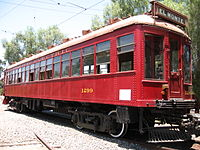 A 1930s streetcar, bright red, showing its front and right side