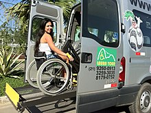 A special lift raises a wheelchair and its occupant in a bus
