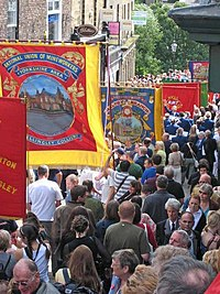 A parade with large traditional trade union banners.