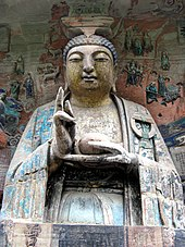 Buddha image gesturing, and surrounded by reliefs depicting stories