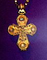 A golden cross decorated with four large gems, depicting Jesus