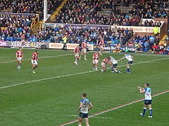 Two rugby league teams playing in front of full stands.