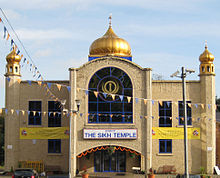 "A large symmetrical two-storey building of yellow brick. The centre bay, incorporating the entrance, juts out. It has a large window with a semicircular top on the first floor and above is a golden onion dome on a blue base. At the ends of the frontage are hexagonal pilasters with small octagonal windowed pavilions and onion domes on top. Above the entrance is a white sign saying ""The Sikh Temple"" in blue. Each side has one two-storey and one one-storey window, and also yellow banners alongside the Temple's name. On each side of the entrance is a wooden seat, and strings of bunting are stretched across the scene."