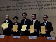 Four men and one woman displaying copies of a report