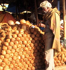 Many stacked coconuts, with man