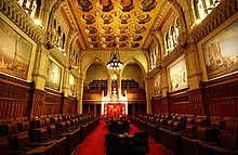 Canadian Senate chamber long hall with two opposing banks of seats with historical paintings