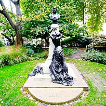 Colour photo of bronze statue of a partly-clothed muse, leaning on a stone pillar, looking up, longingly, at a bronze bust of Sullivan