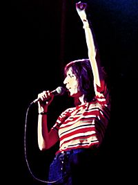 A female singer, Patti Smith, singing into a microphone at onstage performance. She holds the microphone with one hand; the other is raised up and in a closed hand.